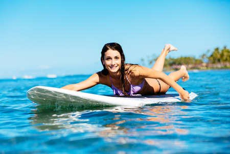 Attractive Young Woman Surfing in Hawaii, Paddling out to the Lineup Imagens