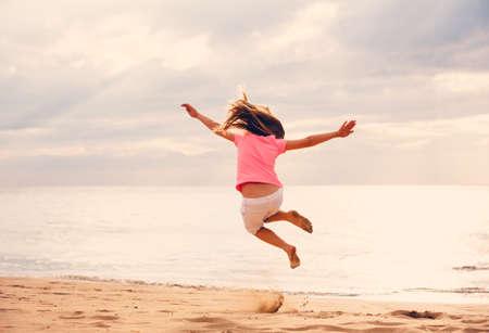 Gelukkig Jong meisje springen van vreugde op het strand bij zonsondergang
