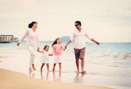 Gelukkig jonge gezin veel plezier op strand bij zonsondergang