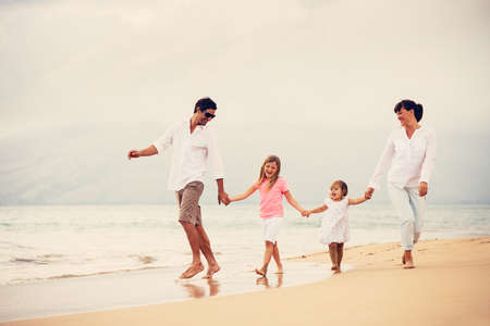 padres e hijos felices: Familia joven feliz divertirse caminando en la playa al atardecer
