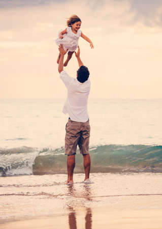 father and child: Father and Daughter Playing Together at the Beach at Sunset. Happy Fun Smiling Lifestyle