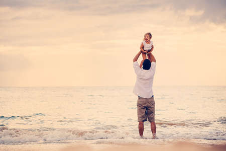Father and Daughter Playing Together at the Beach at Sunset. Happy Fun Smiling Lifestyle photo