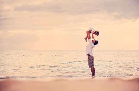 Healthy Father and Daughter Playing Together at the Beach at Sunset. Happy Fun Smiling Lifestyle photo