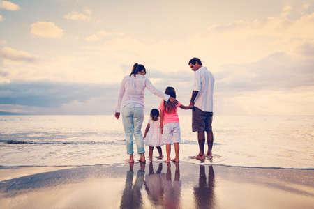 夕暮れ時のビーチで楽しんで幸せな若い家族