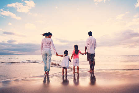 Gelukkige Jonge Familie die Pret op Strand bij Zonsondergang