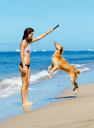 Young Woman Playing with her Adorable Golden Retriever at the Beach, Happy Dog Jumping up into the Air. photo