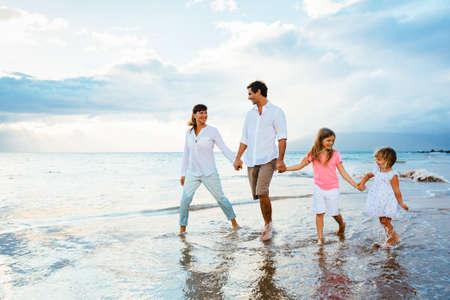 Gelukkig jong gezin lopen op het strand bij zonsondergang. Happy Family Lifestyle Stockfoto