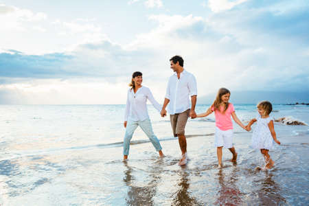 Happy young family walking on the beach at sunset. Happy Family Lifestyle Фото со стока - 27391729