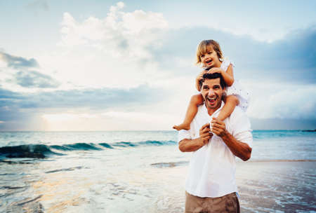 girl bonding: Healthy loving father and daughter playing together at the beach at sunset Happy fun smiling lifestyle Stock Photo