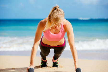 Young attractive woman doing push ups outside with barbells. Fitness woman working out at the beach. Crossfit exercise. Fitness Concept. photo