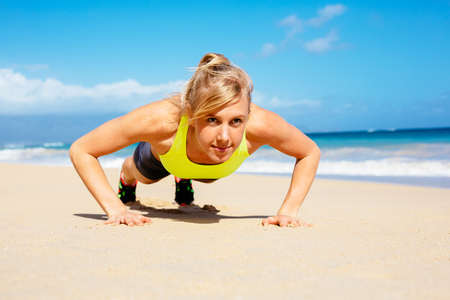 push: Young attractive woman doing push ups outside. Fitness woman working out at the beach. Crossfit exercise. Stock Photo