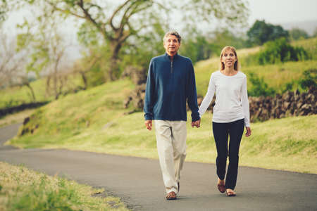 loving hands: Happy loving middle aged couple walking on beautiful country road