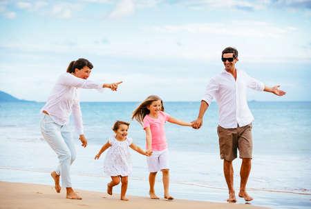 해질녘 해변에 산책하는 행복 한 젊은 가족. 행복한 가족 생활 스톡 콘텐츠