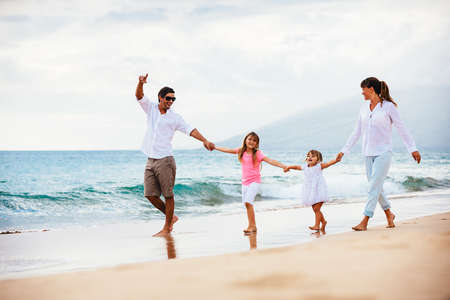 Happy young family walking on the beach at sunset. Happy Family Lifestyle 版權商用圖片 - 27391766