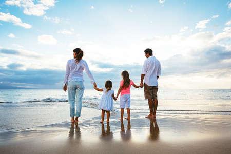 Gelukkige jonge familie kijken naar de zonsondergang op het strand. Happy Family Lifestyle Stockfoto