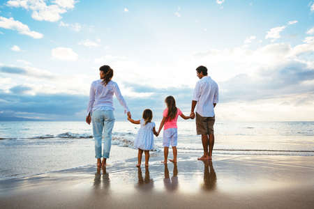 Happy young family watching the sunset at the beach.  Happy Family Lifestyle  Banco de Imagens