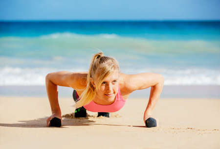 push: Young attractive woman doing push ups outside with barbells. Fitness woman working out at the beach. Crossfit exercise. Fitness Concept. Stock Photo