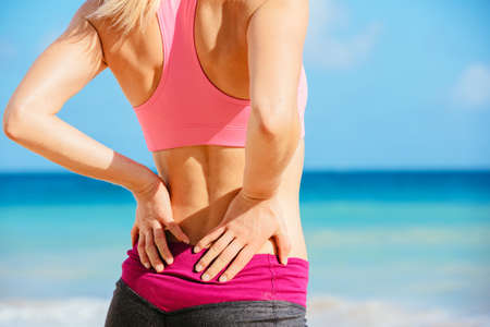 lower back pain: Back Pain. Athletic fitness woman rubbing the muscles of her lower back. Sports exercising injury. Stock Photo