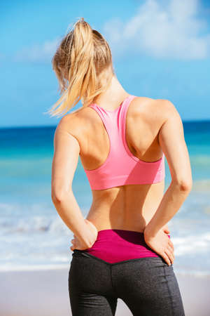 woman back pain: Back Pain. Athletic fitness woman rubbing the muscles of her lower back. Sports exercising injury. Stock Photo