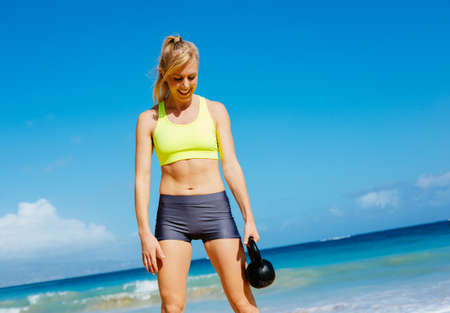 Young attractive woman doing kettle bell exercises outside. Fitness woman working out at the beach. Crossfit exercise. photo
