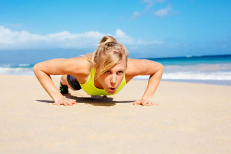 push: Young attractive woman doing push ups outside. Fitness woman working out at the beach. Crossfit exercise. Fitness Concept. Stock Photo