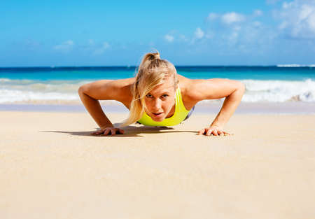 Young attractive woman doing push ups outside. Fitness woman working out at the beach. Crossfit exercise. Fitness Concept. photo