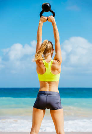 Young attractive woman doing kettle bell exercises outside. Fitness woman working out at the beach. Crossfit exercise. Fitness Concept. photo
