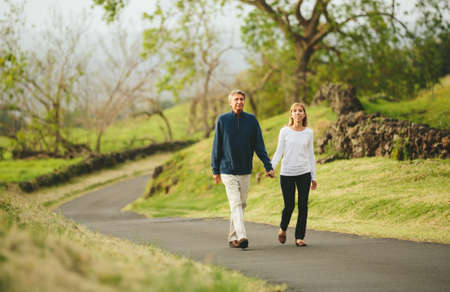 Happy loving middle aged couple walking on beautiful country road