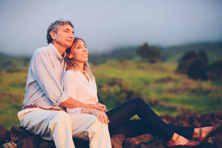 Happy loving middle aged couple, Romantic Moment Watching the Sunset in the Countryside photo