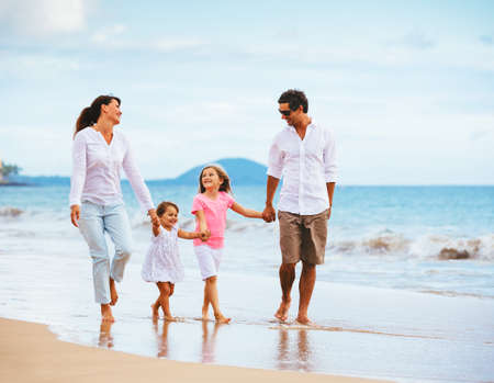 Happy young family walking on the beach at sunset. Happy Family Lifestyle  Stock Photo