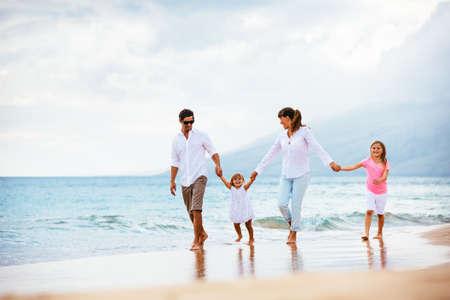 일몰 해변에 산책하는 행복 한 젊은 가족. 행복한 가족의 라이프 스타일 스톡 콘텐츠