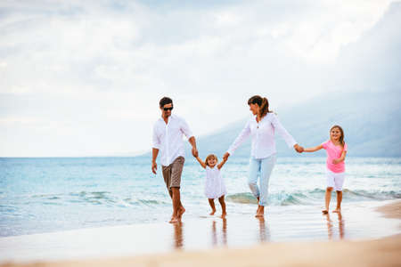 Gelukkig jonge gezin lopen op het strand bij zonsondergang. Happy Family Lifestyle Stockfoto