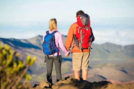 Two hikers relaxing enjoying the amazing view from the mountain top. Looking out over the volcano crater. photo