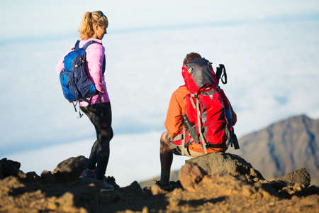 Two hikers relaxing enjoying the amazing view from the mountain top.