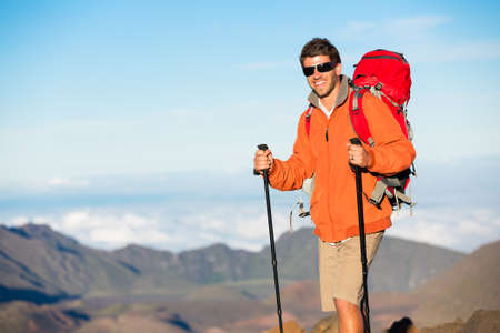 Hiker with backpack standing on mountain top enjoying the view photo