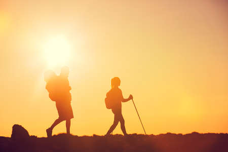 Silhouettes of two hikers with backpacks walking at sunset. Trekking and enjoying the sunset view from mountain top above the clouds. Stock Photo