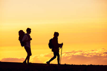 Silhouettes of two hikers with backpacks walking at sunset. Trekking and enjoying the sunset view from mountain top above the clouds. photo