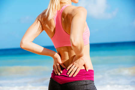 Back Pain. Athletic fitness woman rubbing the muscles of her lower back. Sports exercising injury. Stock Photo