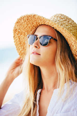 Fashion lifestyle, Portrait of beautiful blond girl on the beach in sunhat and sunglasses. photo