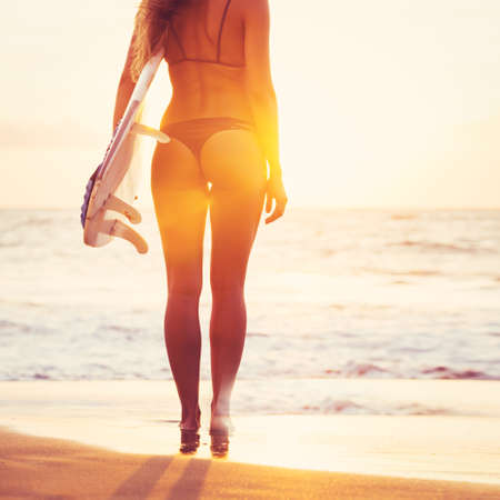 Beautiful sexy surfer girl on the beach at sunset photo