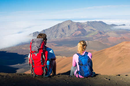 taking a break: Two hikers relaxing enjoying the amazing view from the mountain top. Sitting down taking a break looking out over the volcano crater.