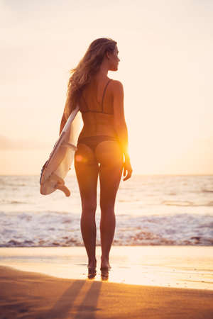 rear view girl: Beautiful sexy young surfer girl in bikini with surfboard on the beach at sunset