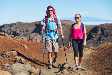 walk in: Hikers enjoying walk on amazing mountain trail. Backpacking in Haleakala volcano, incredible view. Couple trekking.  Stock Photo