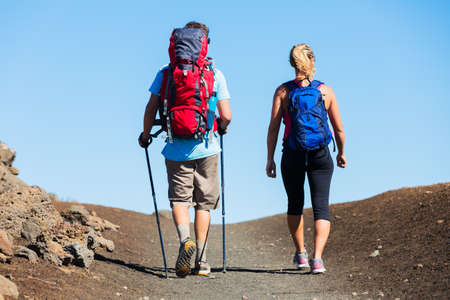 Hiking in the mountains. Athletic couple with backpacks enjoying hike outdoors.