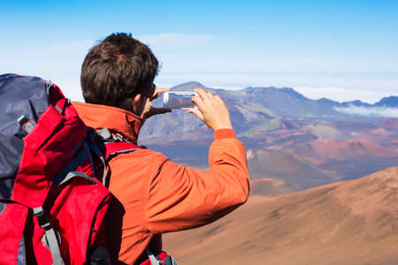 Man taking a photo of the mountains with smartphone photo