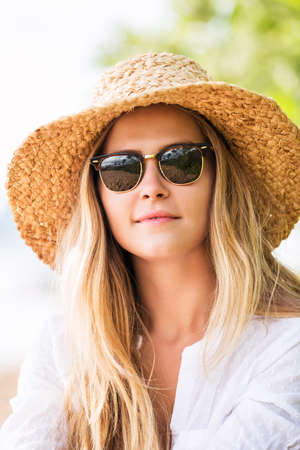 Fashion lifestyle, Attractive woman in sun hat and sunglasses\ at the beach
