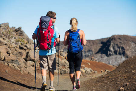 Hiking in the mountains. Athletic couple with backpacks enjoying hike outdoors. photo