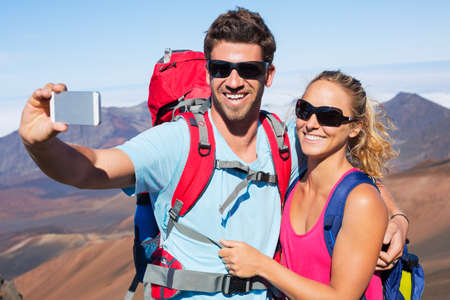 trekker: Happy couple taking photo of themselves with smart phone outdoors, Taking a selfie