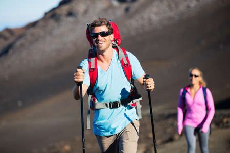 Hiking in the mountains. Happy athletic couple with backpacks enjoying hike outdoors on beautiful mountain trail. photo