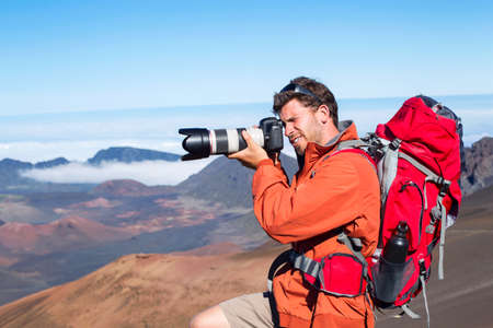 telephoto: Nature photographer taking pictures outdoors on hiking trip in the mountains Stock Photo